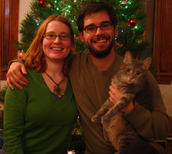Apryl, Hayden, and Eva (the cat) in front of the Christmas tree